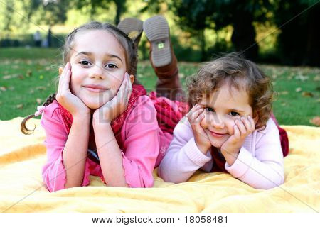 Two beautiful sisters lying on their tummies , outdoor in the autumn park. Focus on older child in front