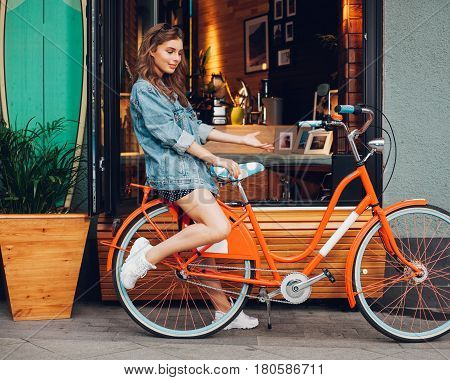 Cute girl in a summer dress, denim jacket, sunglasses sits on the trunk of a red vintage bicycle in LA city. California. Sunny summer. On background surf cafe. Outdoor.