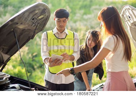 Insurance Concept;Front view of insurance agent writing on tablet while examining car after accident