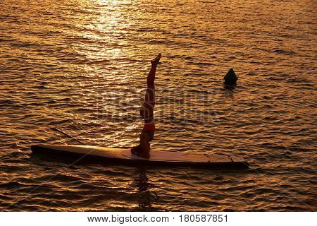 Yoga girl over SUP Stand up Surf board at the ocean sea