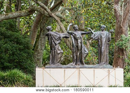 Auckland New Zealand - March 1 2017: Three bronze figures represent the male Auckland in the middle of females Wisdom and Fertility. Green tree background. White stone stand. Claims of being haunted