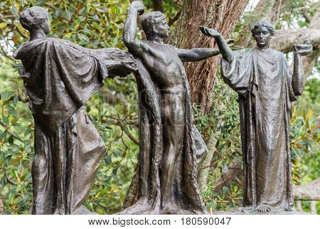 Auckland New Zealand - March 1 2017: Three bronze figures represent the male Auckland in the middle of females Wisdom and Fertility. Green tree background. Claims of being haunted gave name.