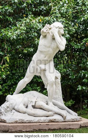 Auckland New Zealand - March 1 2017: Closeup of all white statue of slain Abel with murderer Cain standing over him and holding rock in his right hand. Green tree background.