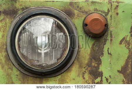 front headlights of an old rusty green truck, closeup