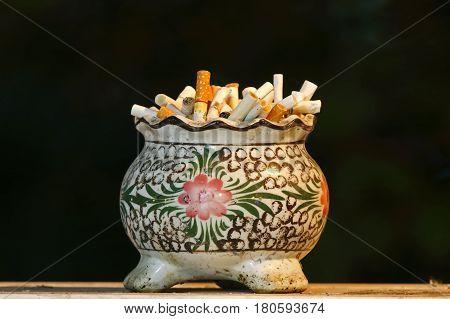 Ashtray ceramic full of cigarette butts smoker
