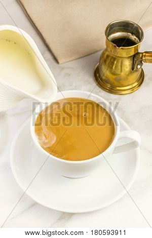 Milk just poured into a cup of coffee, with a vintage coffee pot in the background. Selective focus