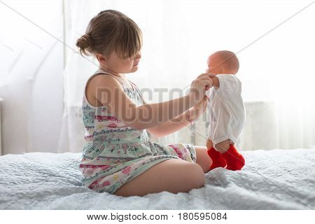Child girl playing with a doll hugging her taking care of a doll life style and childhood real interior
