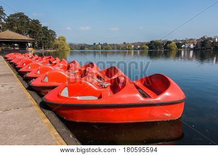 A row of red paddle boats pedalos for recreation parked at Roath Park Lake Cardiff Wales UK.