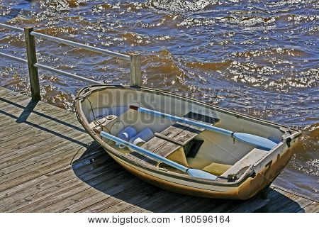 A small row boat sitting on a dock during the day with light colored blue oars resting on the seats and white caps from the waves surrounding it.