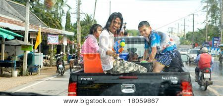 Young Thai man shooting water towards photographer with super soaker from back of pickup truck as the nation celebrates the Thai Songkran Water festival to mark the start of the Thai new year