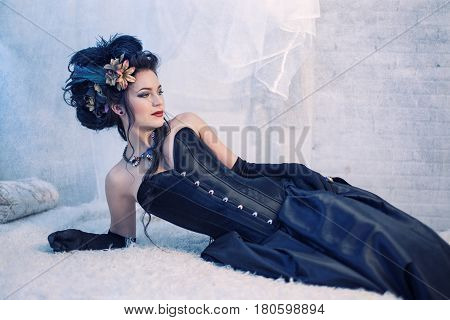 Woman in black dress with hairstyle in rococo style on a light background
