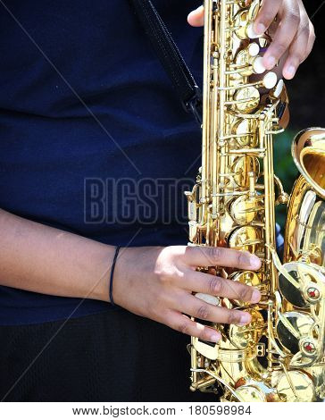 Tenor saxophone being played by a jazz musician performing in concert outdoors.