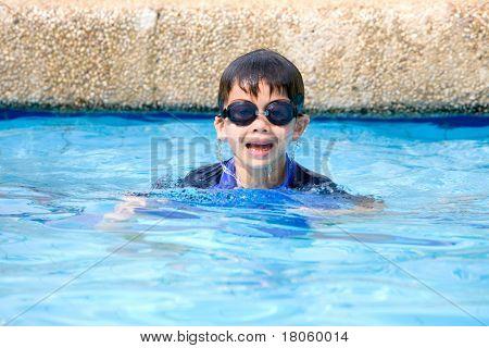 Young boy having fun in the tropical swimming pool