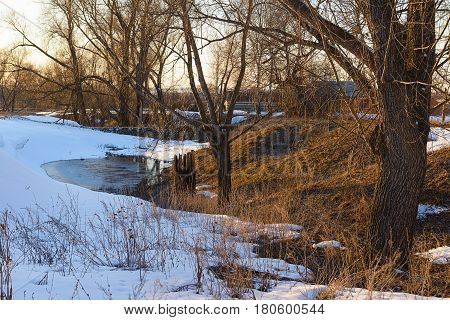 Spring landscape with snowdrifts and a pond