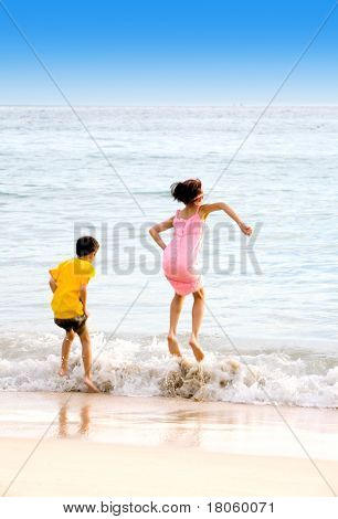 Excited brother and sister jumping above waves at the beach
