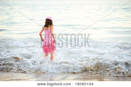 Young girl in pink dress enjoying the sensation of the waves crashing against her legs.