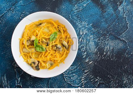 Top view of spiralized butternut squash pasta made with coconut milk curry sauce and mushrooms on blue stone table selective focus copy space for text