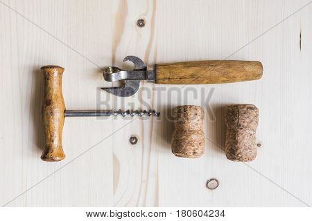 Vintage beer bottle opener , two corks and corkscrew with wooden worn handles of pleasant light brown color lying on a wooden table.Bar stuff concept