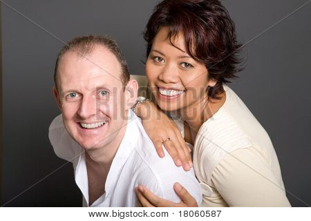 Happy inter-marriage couple of Asian woman and European man.