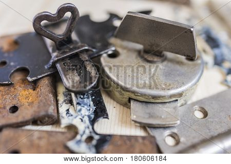 Old vintage locks and door hinges rusted and frayed with peeling paint lying in a pile on a light wooden background
