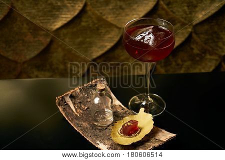 Fresh branded red alcoholic cocktail with a small bottle for alcohol and a red marmalade snack on a black stone bar counter. Concept of alcoholic and non-alcoholic bar beverage.