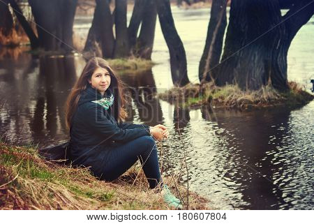 The girl sits on the river bank