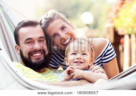 Happy parents playing with their baby boy in hammock