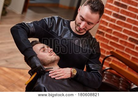 Hairdresser is shaving male beard with the knife against brick wall at the barbershop. Handsome bearded man is getting shaved by hairdresser. Black clothes. Professionalism and craftsmanship.