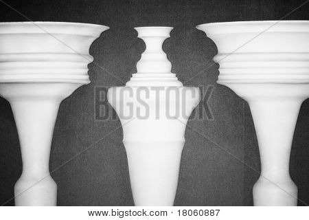 Optical illusion created by clay columns forming shapes of two ladies talking