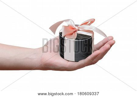 gift in the form of mobile portable speaker, tied with a pink ribbon in man's hand