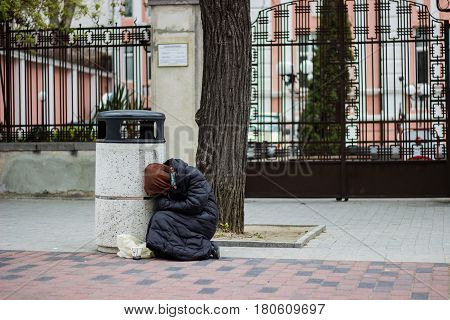 Homeless beggar woman sitting on the asphalt asking for money for food
