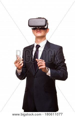 Young handsome businessman in black suit wearing virtual reality goggles., isolated on white background.