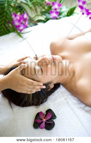 Woman restful while having a head massage therapy in spa