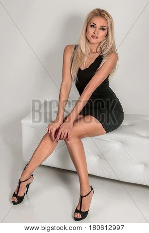 Portrait Of Pretty Fashionable Girl Who Is Sittng In The Studio