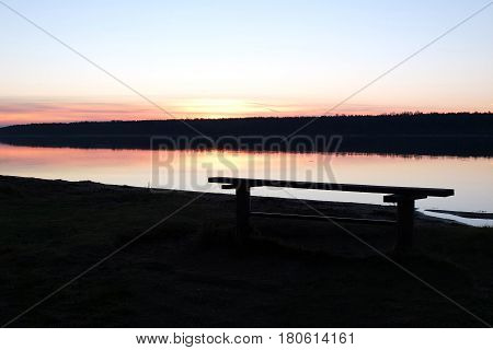 Conceptual scene on the coast of river and deserted bench. Landscape at sunset and bench for inspection and admiration. Idyllic holiday romantic evening.