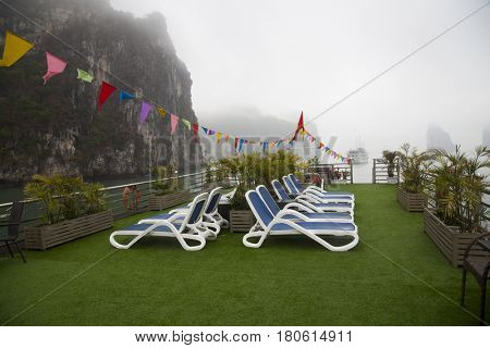 Boat upper deck with blue beach chairs, empty, no people, overlooking Halong bay, Vietnam
