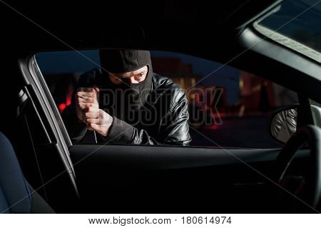Male carjacker open car door with screwdriver