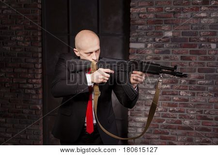 Killer in suit and red tie shoot a machine gun