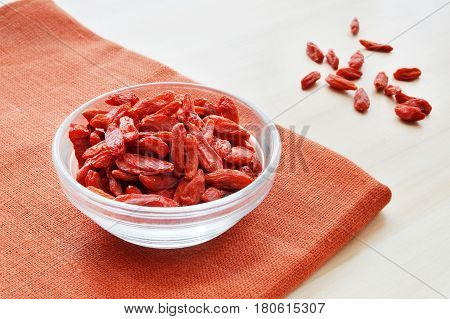 red goji berry in a glass bowl over terracotta flax background healthy food concept