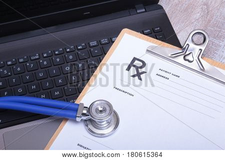 Prescription form with laptop computer and stethoscope.