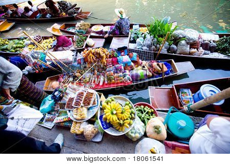 Bangkok August 2008.Wooden flat boats busy ferrying people at Damoen Saduak floating market. A traditional but popular method of buying and selling still practised in the canals of Bangkok Thailand.