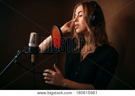 Female singer recording a song in music studio