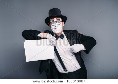 Male mime actor with empty paper sheet
