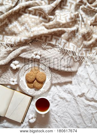 Breakfast in bed - oatmeal cookies and a cup of tea. Warm, soft, light colors in the photo. Warm plaid, cotton flowers, notepad in the frame. Copy spase. Flat lay style.