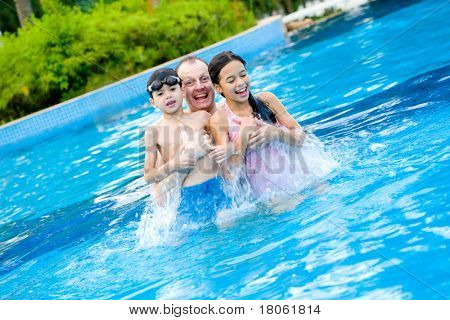 Man with two children enjoying the swimming pool