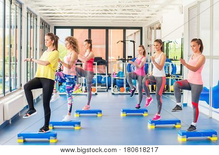 Group Of Beautiful Young Women Working Out On Blue Stepper And Smiling. Knee Up.