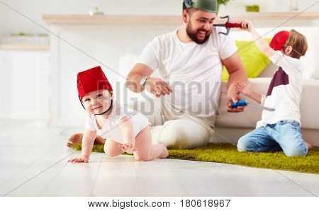 Father With Sons Playing In War Games At Home