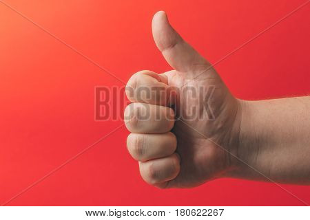 Close-up of male plump hand showing thumbs up on red background