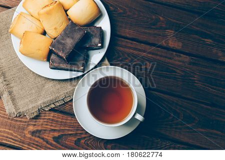 Cup of tea and biscuits with a square marshmallow in chocolate on an old wooden table, top view, toned, space for text