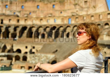 ROME, ITALY - MAY 10, 2014: The redhead female tourist looks at the Colosseum in Rome, Italy. The Colosseum is an important monument of antiquity and is one of the main tourist attractions of Rome.